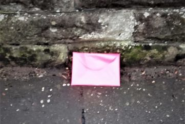Was this pink envelope dropped, thrown away, or deliberately posed?