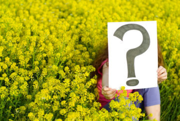 little girl holds a question mark sign in a field of yellow flowers. gardening expert