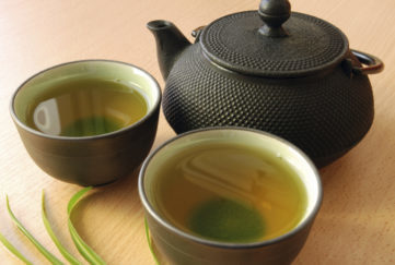 Cast iron teapot with two cups of green tea.